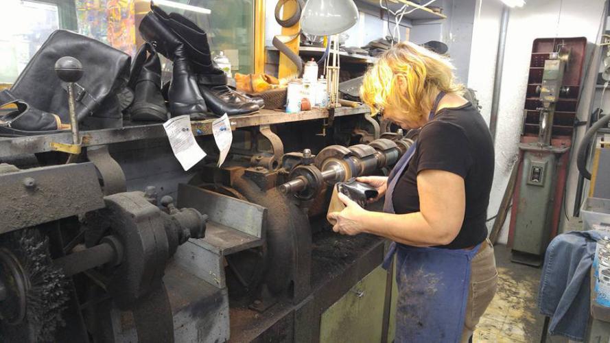 Cordonnière en train de réparer des bottes